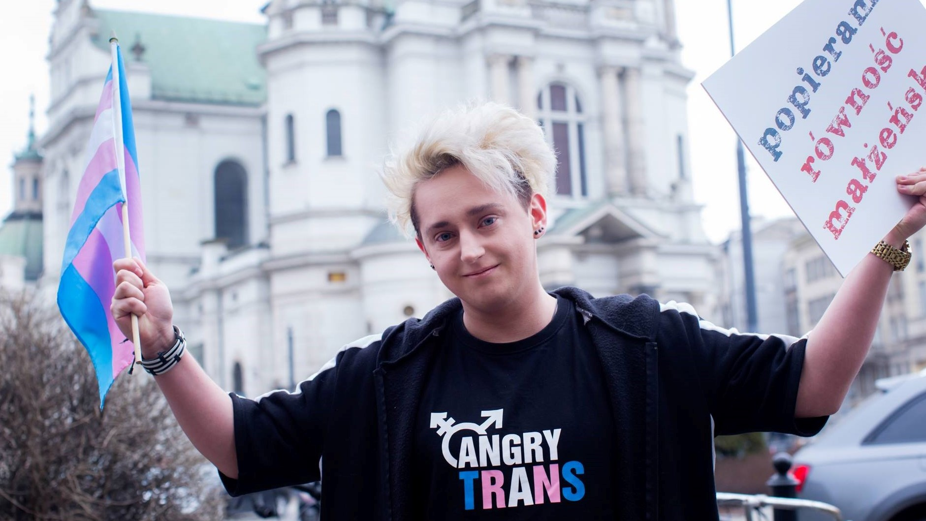 """Na zdjęciu Grzegorz z Angry Trans, w jednej dłoni trzyma flagę osób transpłciowych, w drugiej - tabliczkę z napisem """"Popieram równość małżeńską""""."""
