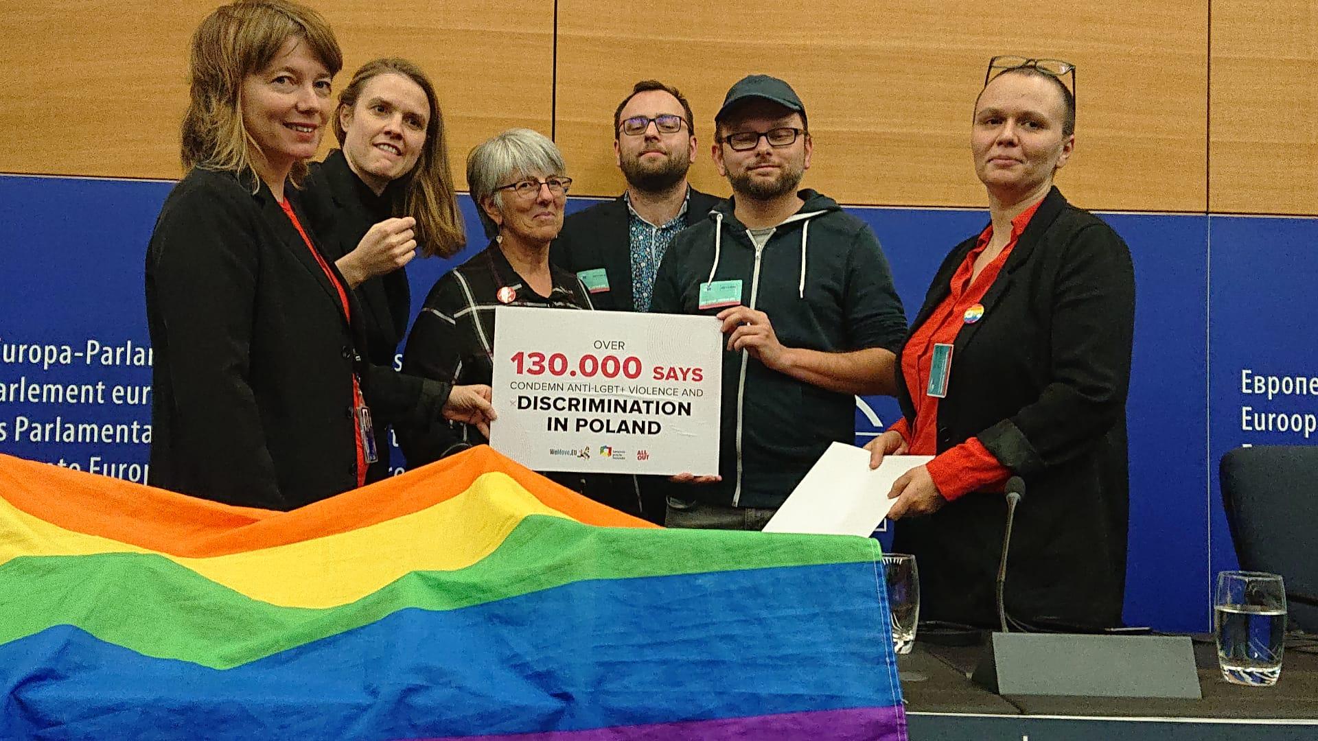 Zdjęcie przedstawia grupę ludzi trzymających tabliczkę z napisem: 130.000 podpisów przeciwko uchwałom anty-LGBT (po angielsku) i tęczową flagą